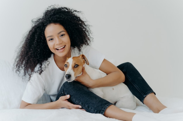 Glad afro woman rests in bed with dog have playful mood pose together in bedroom against white background
