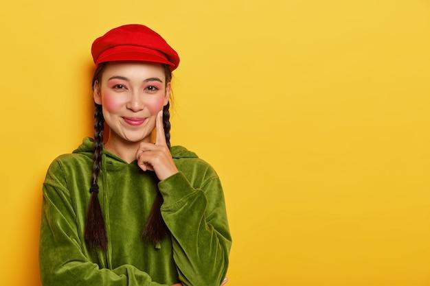기쁜 아시아 소녀는 뺨에 검지 손가락을 유지하고 카메라를 즐겁게 보며 루즈 볼을 가지고 있으며 빨간색 베레모와 녹색 벨벳 스웨트 셔츠를 입습니다.