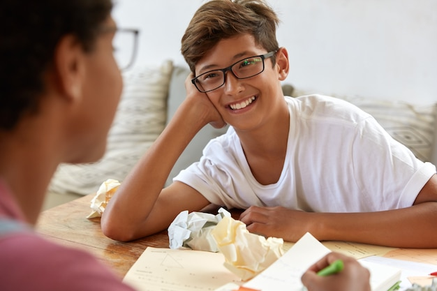 Glad asian male hipster wears optical glasses, casual white t shirt, answers questions during interview, unrecognizable journalist sits back, writes down notes in notepad. teenagers work together