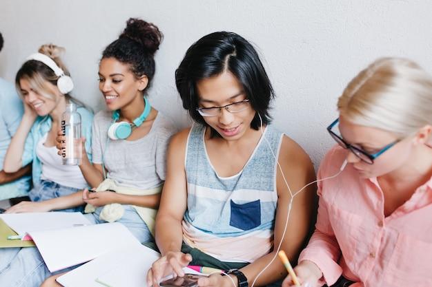 彼の魅力的な金髪の友人が講義を書いている間、スマートフォンでメッセージを入力してうれしいアジアの学生。イヤホンで男の子と女の子と大学の仲間の屋内グループの肖像画。