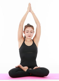 Glad asian woman close eyes and raising arms while meditating in lotus pose during yoga session against white background