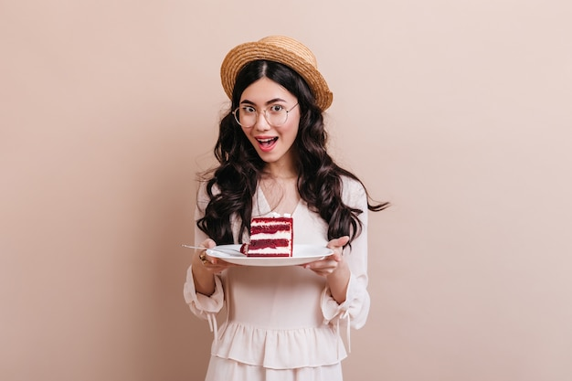 Glad asian woman holding plate with cake. studio shot of chinese woman in straw hat.