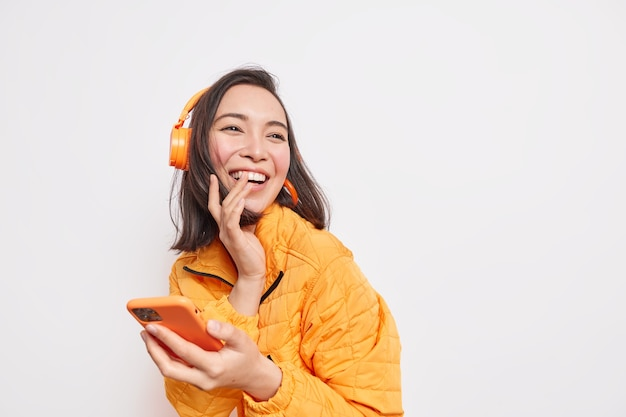 Glad asian woman laughs happlily looks away into distance enjoys favorite music playlist uses mobile application wears wireless headphones dressed in orange jacket isolated on white wall blank space