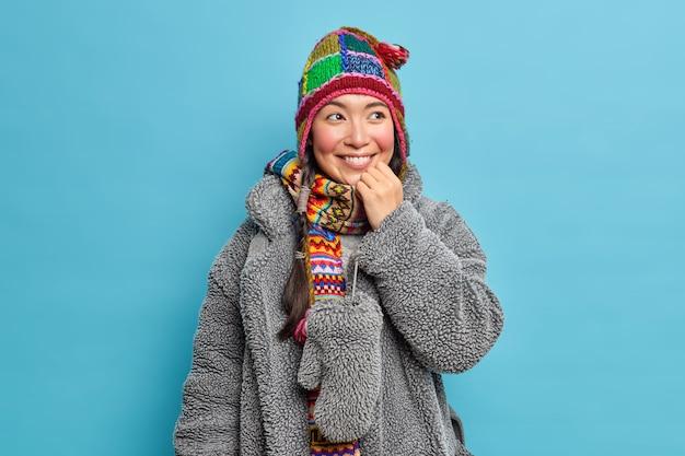 Радостная азиатская женщина носит вязаный шарф шапки и серое пальто из натурального меха, улыбается позитивно и имеет хорошее настроение, изолированное за синей стеной.