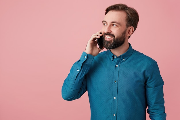 嬉しい魅力的なあごひげを生やした男、目をそらして笑って、デニムシャツを着て、電話で話している。ピンクの背景に分離。