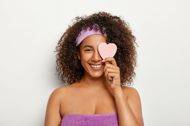 Glad attractive dark haired young woman keeps cosmetic sponge on eye, wears headband, stands wrapped in towel, smiles broadly