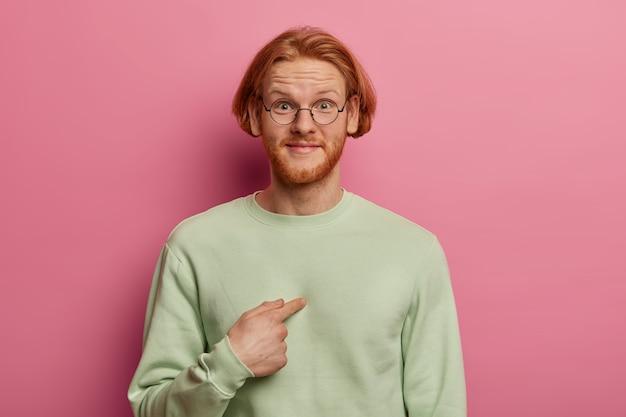 Felice ragazzo barbuto con i capelli rossi e la barba indica se stesso