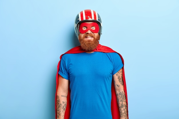Glad bearded man with funny outlook, comes on costume party, being superhero character