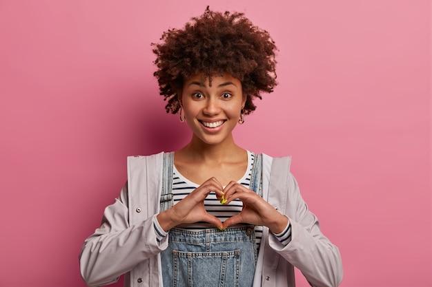 기쁜 아름다운 아프리카 계 미국인 여성이 심장 제스처로 손을 만들고, 모두에게 사랑을 표현하고, 광범위하게 미소를 짓고, 하얀 치아를 보여주고, 성실한 감정을 가지고, 캐주얼하게 옷을 입고, 장밋빛 벽에 고립