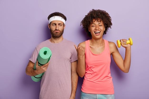 불만족스러운 표정으로 남편에게 아프로 헤어 스타일을 가진 기쁜 아름다운 여인이 엄지 손가락을 가리키고 함께 운동을하고 스포츠 옷을 입으십시오. 화난 사람은 체력 훈련을 열망하지 않습니다.