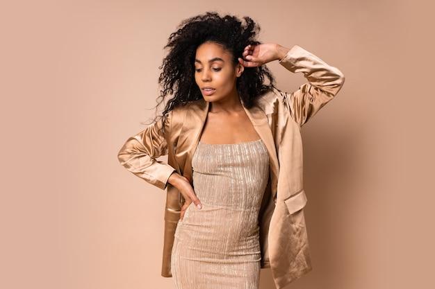 갈색 피부와 우아한 파티 복장 포즈에 볼륨 곱슬 헤어 스타일을 가진 기쁜 아름 다운 여자.
