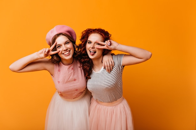Glad best friends posing with peace sign. studio shot of caucasian girls in trendy attire gesturing on yellow background.