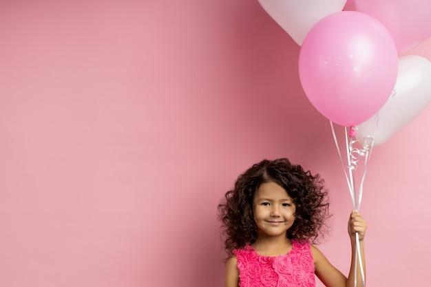 Радует день рождения маленькая девочка с кудрявыми темными волосами, держащая летающие шары, счастливо улыбаясь, в праздничном платье, стоя с копией пространства для вашего текста. праздник, концепция вечеринки.