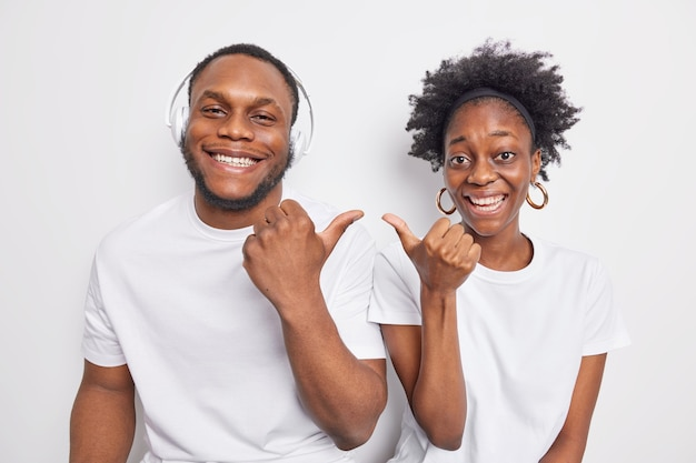 Glad black afro american girlfriend and boyfriend point at each other smile positively