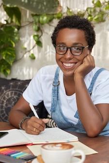 기쁜 흑인 여성 작가가 투명한 안경을 쓰고 피어싱