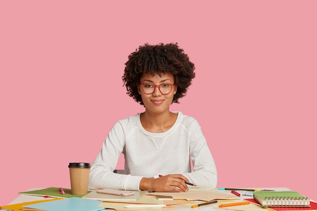 嬉しい黒人イラストレーターがクレヨンを持ってスケッチをし、仕事にインスピレーションを与え、優しい笑顔