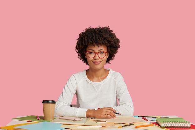 Glad black illustrator holds crayon, makes sketches, has inspiration for work, gentle smile