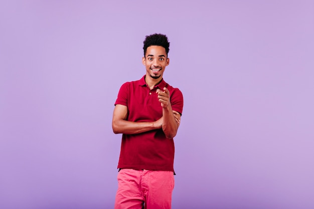 Glad black man in summer outfit posing on violet wall. carefree brunette guy expressing good emotions.