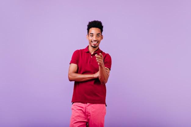 Felice uomo nero in abito estivo in posa sulla parete viola. ragazzo bruna spensierato che esprime buone emozioni.