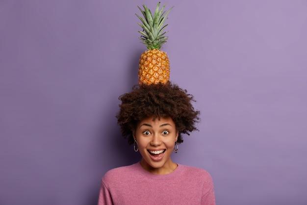 Довольная темнокожая женщина с вьющимися волосами, держит ананас над головой, радостно хихикает, наслаждается летним отдыхом, показывает зубы и смотрит в камеру.
