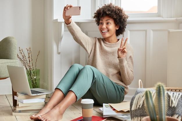 Glad black woman makes peace sign