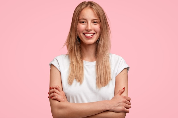 Glad blonde woman model keeps arms folded, has toothy smile, rejoices meeting with best friend, share impressions after party, dressed in white t shirt