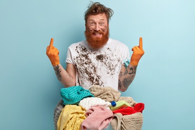 Glad blue eyed redhead man with thick bristle, has dirty white t shirt, wears rubber gloves, shows middle finger with both hands, stands near basin of laundry, isolated over blue wall.