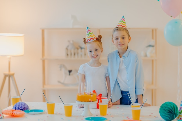 Glad boy and his small ginger sister dressed in festive clothes, party hats, celebrate birthday together
