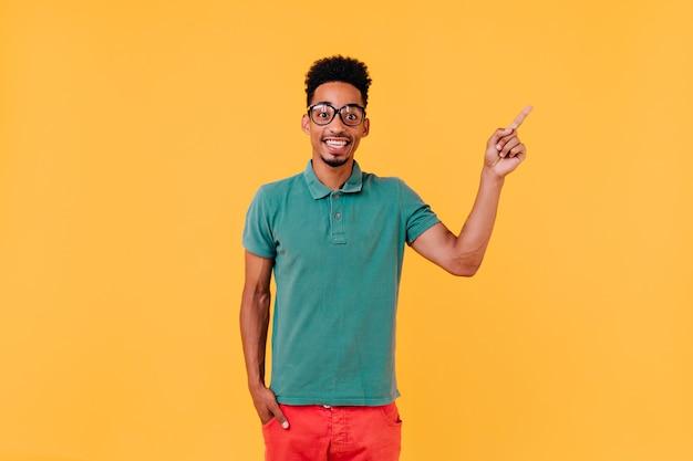 기쁨과 함께 포즈 녹색 티셔츠에 다행 소년. 긍정적 인 감정을 표현하는 유행 복장에 웃는 남자의 실내 사진.