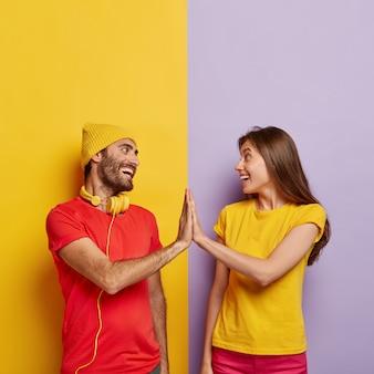 Рады, что парень и девушка трогают ладони, позитивно улыбаются, о чем-то соглашаются, одеты в красно-желтые повседневные футболки