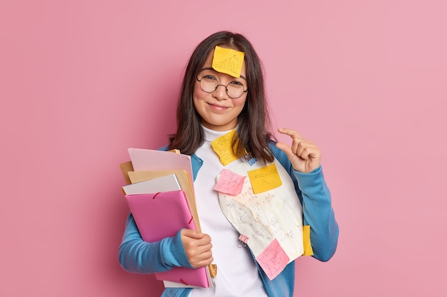 Glad brunette schoolgirl makes tiny gesture tells she needs little more time for exam preparation has sticky note stuck on forehead has deadline to finish project work.