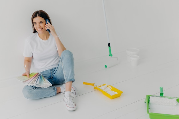 Glad brunette woman in casual clothes holding color samples