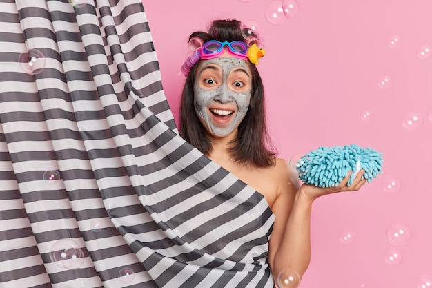 Glad brunette young asian woman undergoes beauty procedures takes shower in bathroom holds sponge applies clay mask has happy expression poses against pink background with soap bubbles around