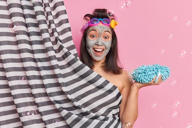 Довольная брюнетка молодая азиатская женщина проходит косметические процедуры, принимает душ в ванной, держит губку, наносит глиняную маску, имеет счастливое выражение лица на розовом фоне с мыльными пузырями вокруг