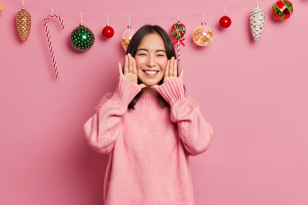 Glad brunette young mixed race woman smiles broadly keeps palms near rouge face expresses positive emotions wears sweater awaits for holiday event poses