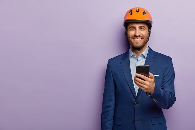Glad businessman posing in classy suit and red helmet at the office