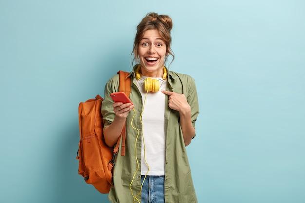 嬉しい白人女性が自分を指さし、なぜ私に尋ねる、幸せな表情をしている、ステレオヘッドホンに接続された携帯電話を持っている