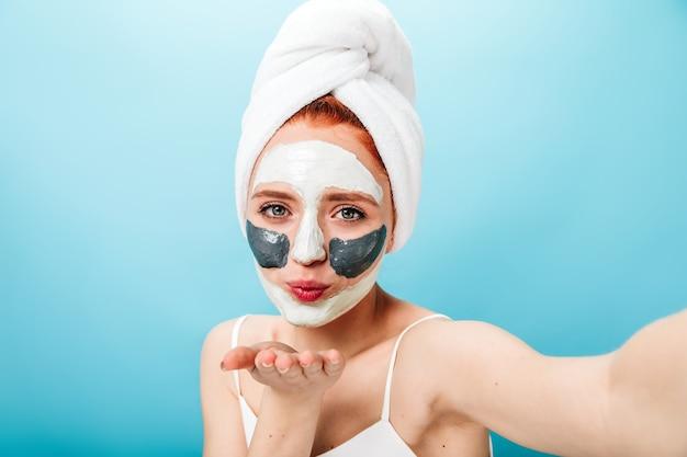 エアキスを送信するフェイスマスクを持つ嬉しい白人の女の子。スキンケア治療と自分撮りをしている美しい女性。
