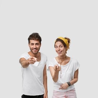 Довольные кавказские женщина и мужчина указывают, сосредотачиваются на руках, демонстрируют что-то позитивное