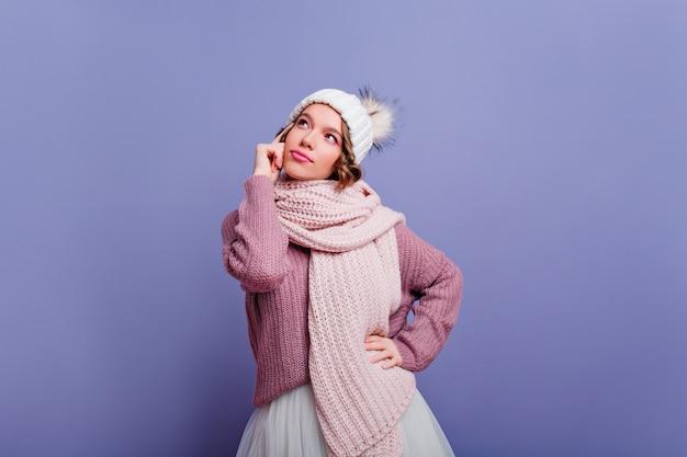 Felice donna caucasica in elegante sciarpa lavorata a maglia in posa con interesse. ritratto dell'interno della signora riccia ispirata isolata sulla parete variopinta.