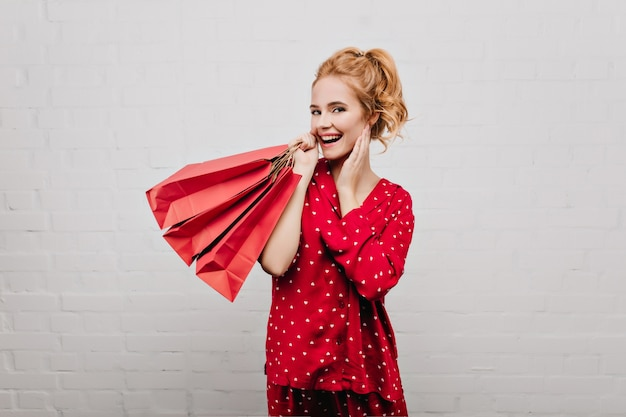 Glad caucasian woman wears cotton red pajamas posing with paper bags. indoor portrait of emotional blonde girl with gifts isolated on light wall