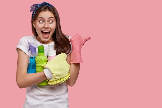 Glad caucasian woman with positive expression, wears rubber gloves, points aside with thumb, holds spray and detergent in hands