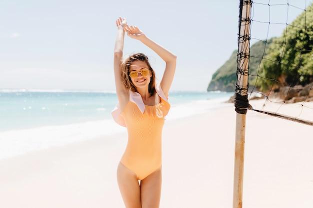 エキゾチックな島でおかしいダンスをしている嬉しい白人の若い女性。バレーボールセットの近くで身も凍るようなオレンジ色の水着姿の格好良い女の子の屋外写真。