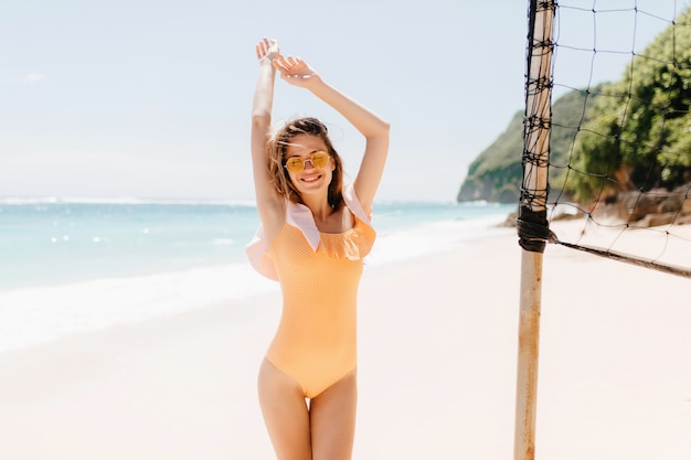 Glad caucasian young lady funny dancing at exotic island. outdoor photo of shapely pleasant girl in orange swimwear chilling near volleyball set.