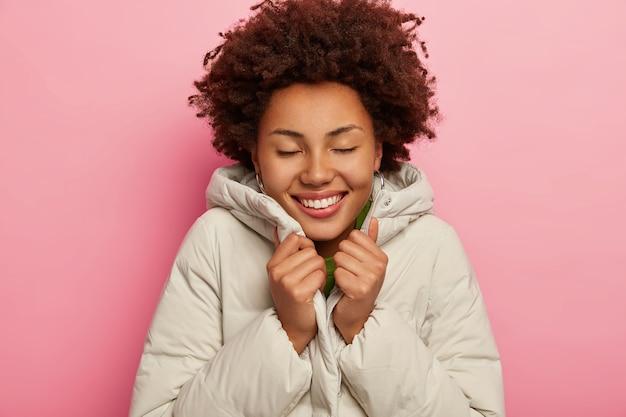 Felice ragazza affascinante si sente calda in giacca bianca, sorride ampiamente, tiene gli occhi chiusi, mostra denti perfetti, si erge su sfondo rosa studio
