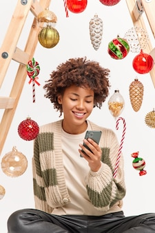 Glad charming millennial girl with afro hair scrolls social media via smartphone sits relaxed indoor takes break after decorating home for coming winter holidays surfs internet makes shopping online