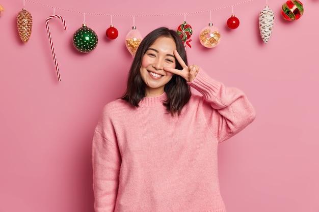 歯を見せる笑顔の黒髪の嬉しい魅力的な女性は、平和のジェスチャーがカジュアルなセーターに身を包んだ前向きな感情を表現し、お祭り気分のポーズをとる