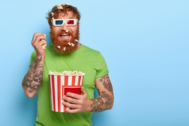 Glad cheerful red haired man stares at camera through cinema glasses