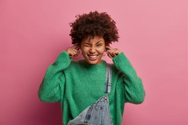 嬉しい陽気な女性は耳をふさぎ、何か大きな音と騒音を聞きます