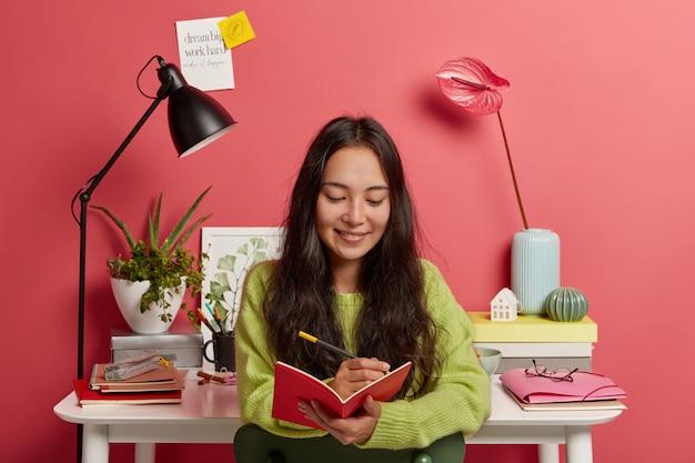 Felice donna concentrata concentrata nel blocco note, annota idee per saggi o lavori di ricerca, compone una recensione, posa contro il posto di lavoro con la lampada da scrivania